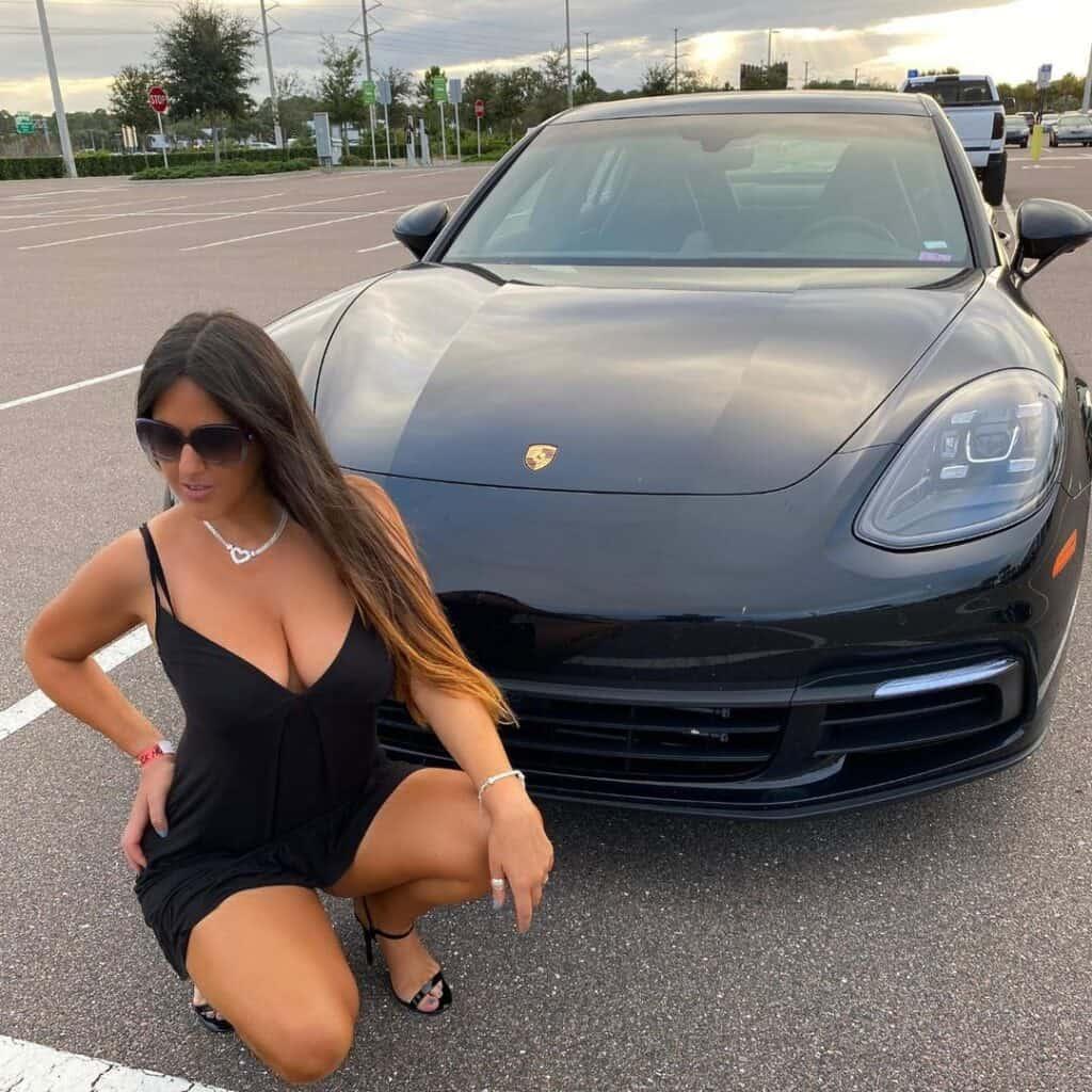 Claudia Romani posing infornt of her car.